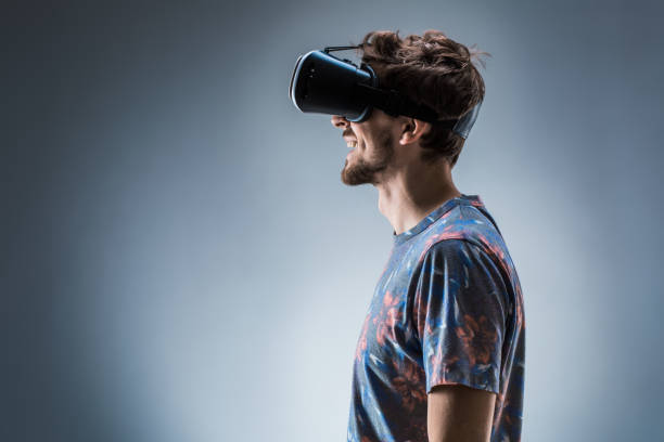side view of a young guy using a vr headset. emotions - ritratto 360 gradi foto e immagini stock