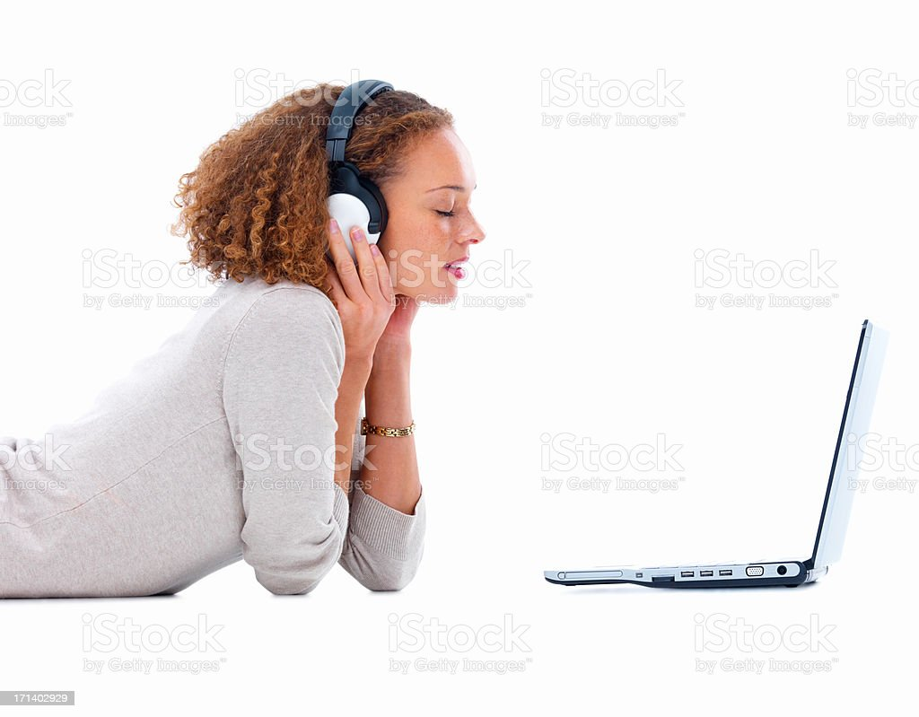 Side view of a young lady with headphones and laptop isolated on white background stock photo