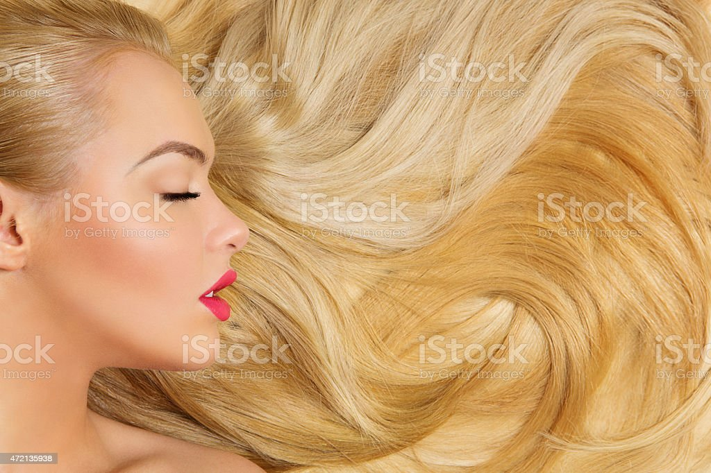 Side view of a young woman's head with long blonde hair stock photo