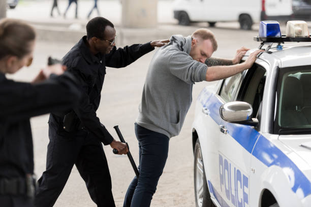side view of african american arresting man while policewoman aiming at him by handgun side view of african american arresting man while policewoman aiming at him by handgun arrest stock pictures, royalty-free photos & images