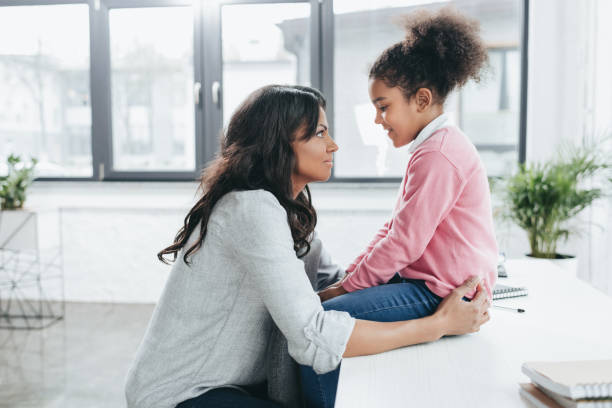 side view of african american mother talking with her daughter indoors stock photo