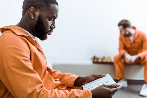 vue latérale d'un prisonnier afro-américain lecture livre - prison photos et images de collection