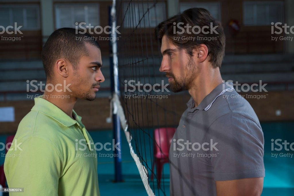 Side view of aggressive male volleyball players looking at each other stock photo
