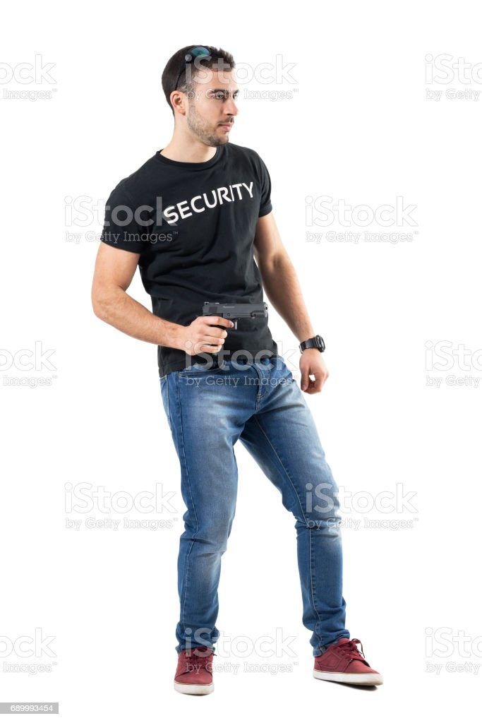 Side view of alerted young cop holding gun looking away. stock photo