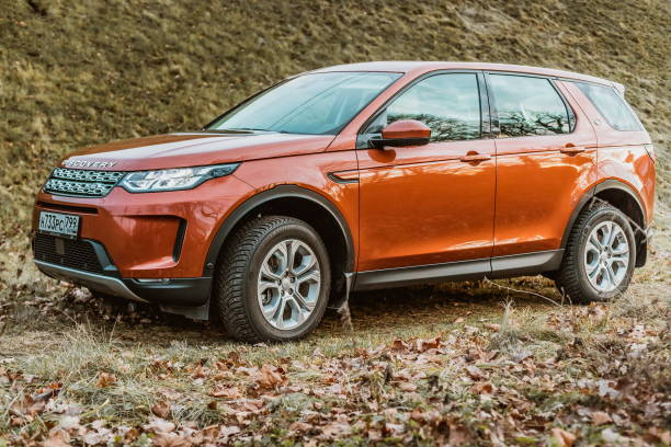 side View of all new premium england suv. Land rover Discovery sport parked in the forest. Orange all wheel drive car standed on the ground. stock photo