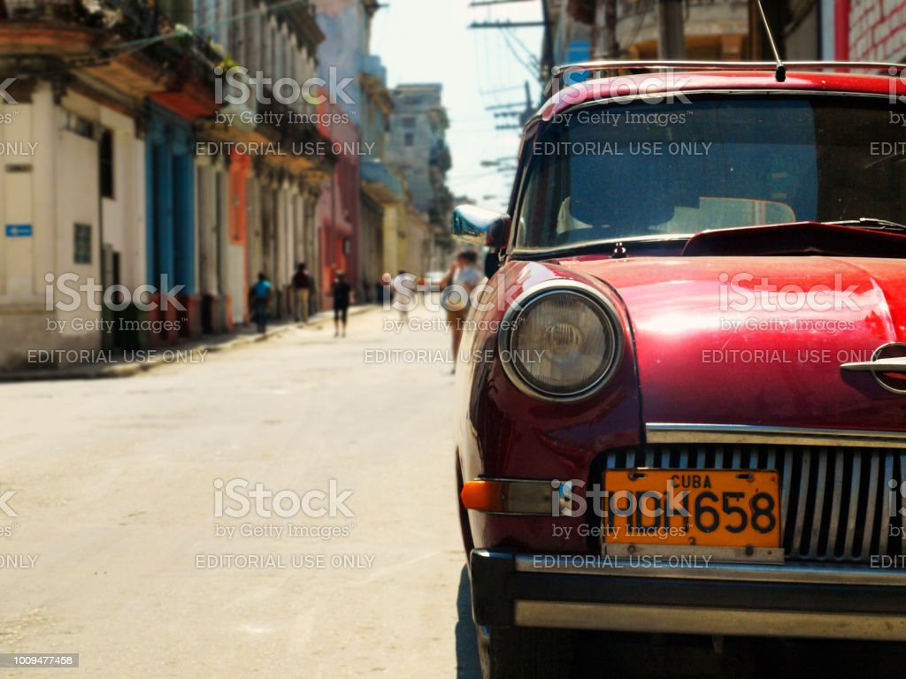 Havana, Cuba - June 21, 2018: Side view of an antique American-made red automobile parked in the old street of the city. stock photo