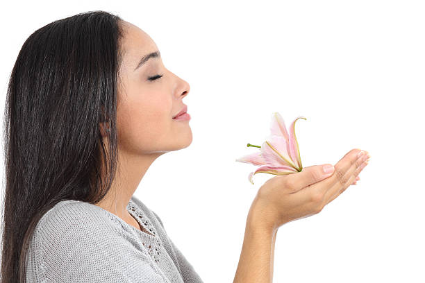 side view of an arab woman smelling a flower - scented stock photos and pictures
