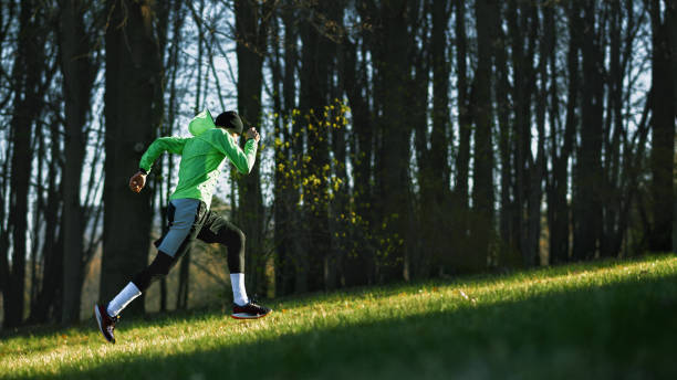 Side view of an athlete young man running on a hill in mountain. Athletic male jogging in the park in the morning in a sunny day. People, healthy lifestyle and sport concept stock photo