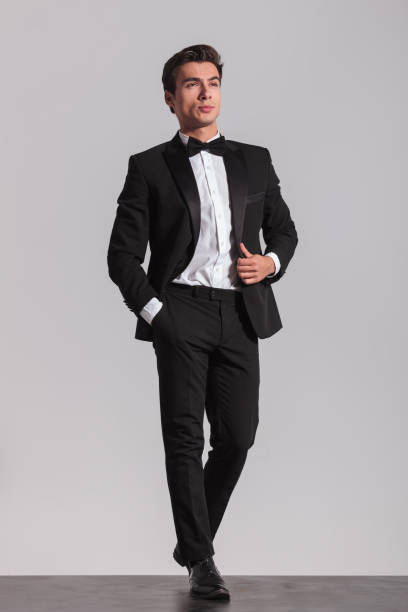 side view of an elegant man walking in studio - tuxedo stock photos and pictures