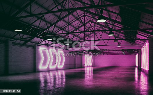 Side view of an empty large and long warehouse interior with cement floor, illuminated by lots of pink arrow shaped neon lights from side brick walls. A large blank brick wall background with copy space at the end. Slight vintage effect applied. 3D rendered image.
