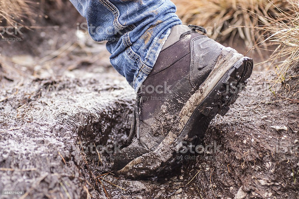 Side view of an hiking shoe covered in mud stock photo