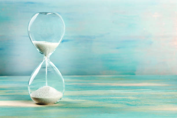A side view of an hourglass with falling sand, on a teal background with copy space stock photo