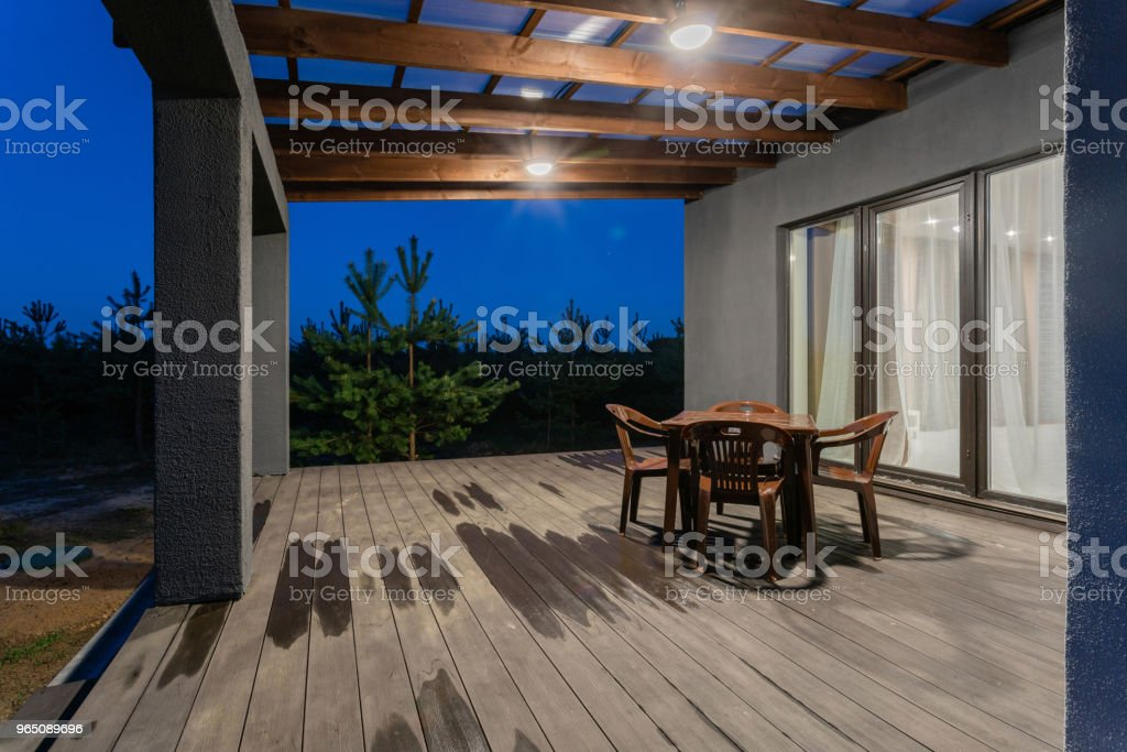 Side view of an open veranda in front of a modern forest cottage. Pine young forest under the sunset rays in the background. royalty-free stock photo