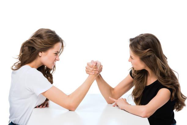 seitenansicht der böse zwillinge armwrestling am tisch isoliert auf weiss - armdrücken stock-fotos und bilder