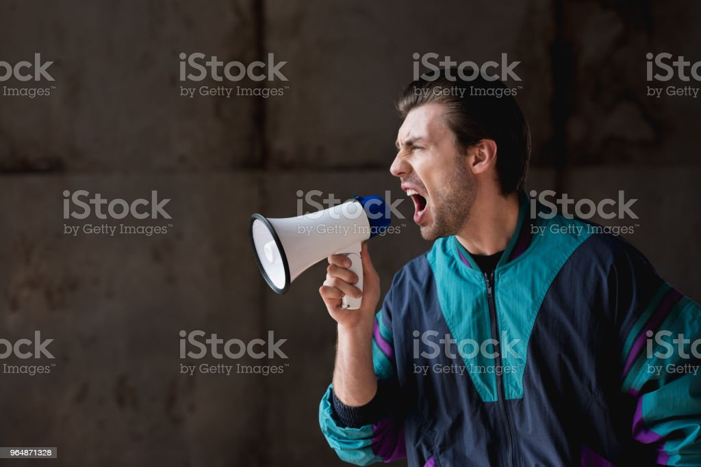 side view of angry young man in vintage windcheater shouting with loudspeaker royalty-free stock photo