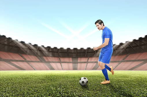 Side view of asian football player man kicking the ball on the field