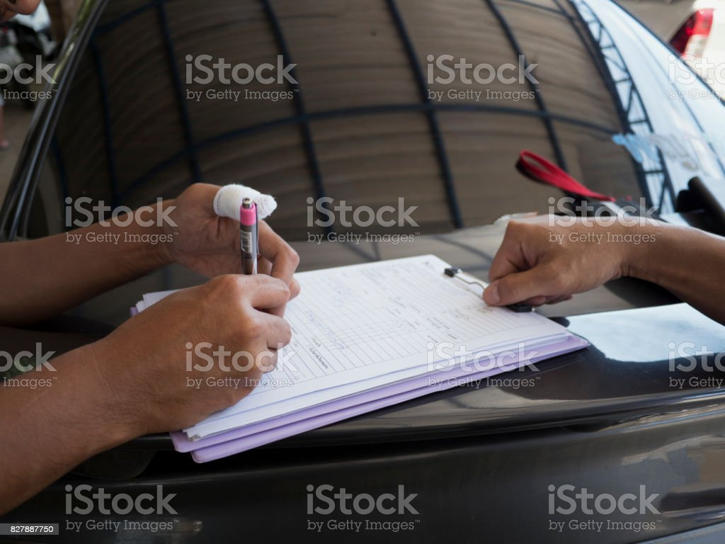 Side View Of Asian Man Writing On Papers Insurance Agent Examining