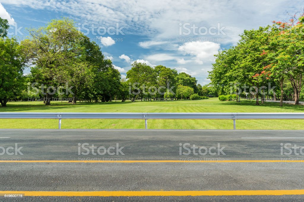 Side view of asphalt road with green grass field in park stock photo