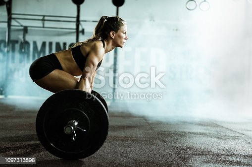 Muscular build woman exercising deadlift with barbell in a health club. Copy space.