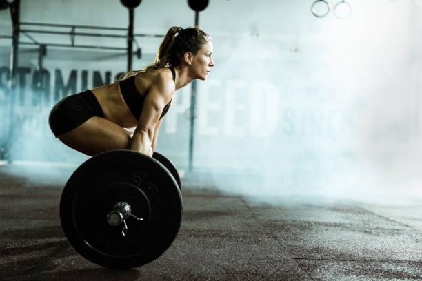 vista lateral de mujer atlética ejercicio de peso muerto en un gimnasio. - culturismo fotografías e imágenes de stock