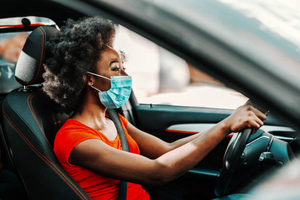 Side view of attractive african woman with short curly hair with face mask on sitting and driving car. Prevention from spreading corona virus / covid 19 concept. stock photo