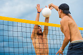 Side view of two male volleyball players in the attractive action on the net
