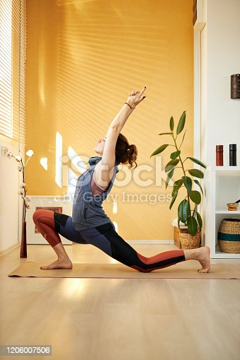 istock Side view of attractive middle aged brunette in  Warrior I pose. Home interior, morning time. 1206007506