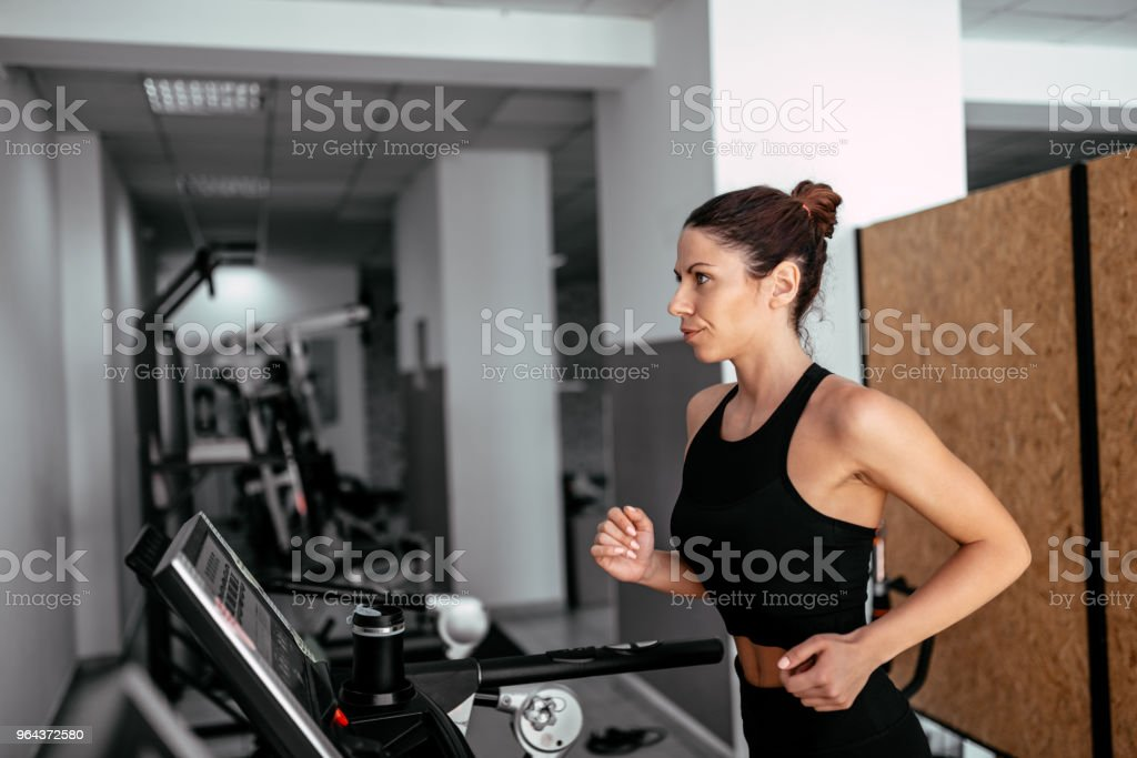 Vista lateral da mulher atraente esportes correndo na esteira. - Foto de stock de Academia de ginástica royalty-free
