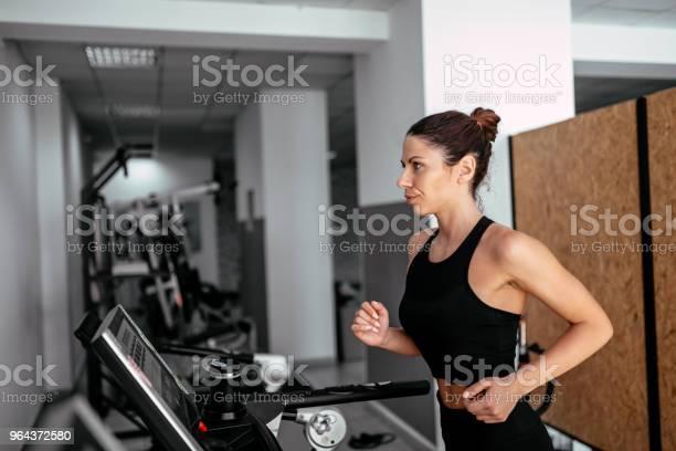 Foto de Vista Lateral Da Mulher Atraente Esportes Correndo Na Esteira e mais fotos de stock de Academia de ginástica