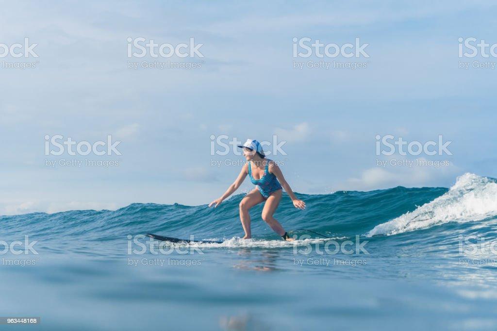 Okyanusta Sörf yüzme elbiseli çekici kadın yan görünüm - Royalty-free Bali Stok görsel