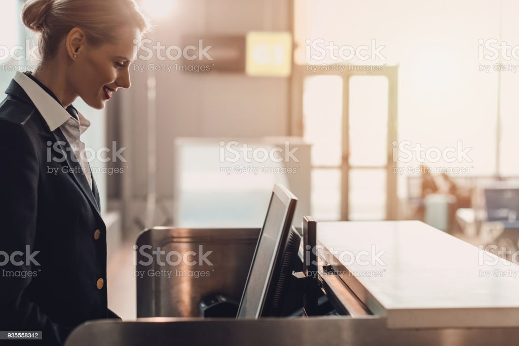 side view of attractive young airport worker at workplace at airport check in counter stock photo