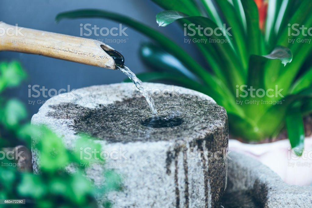 side view of bamboo spout pouring water on stone stock photo