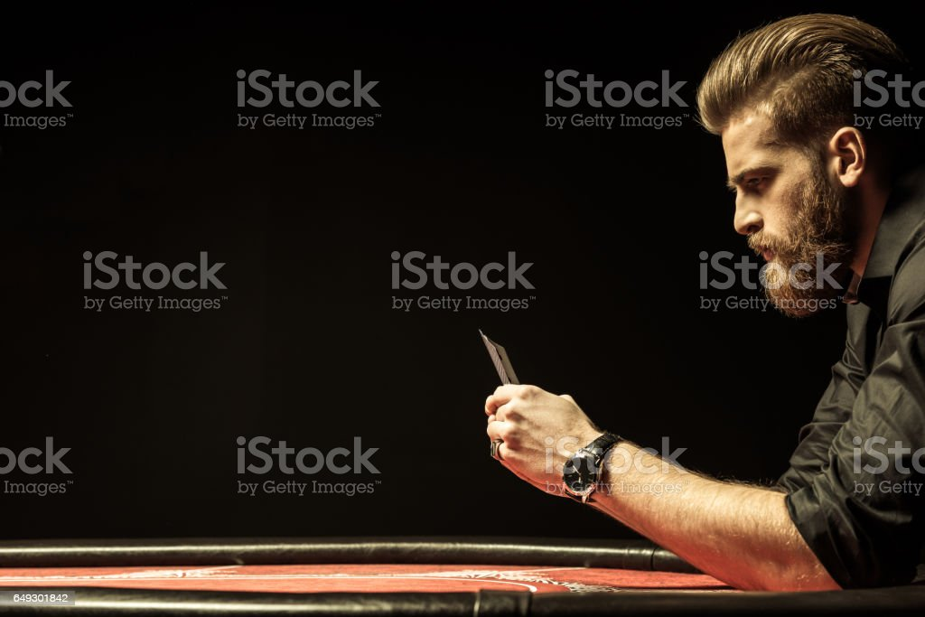 Side view of bearded man holding poker cards on black stock photo