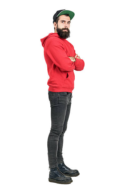 Side view of bearded man in hoodie wearing baseball cap Side view of young bearded man in red hoodie wearing baseball cap with crossed arms. Full body length portrait isolated over white studio background men in tight jeans stock pictures, royalty-free photos & images