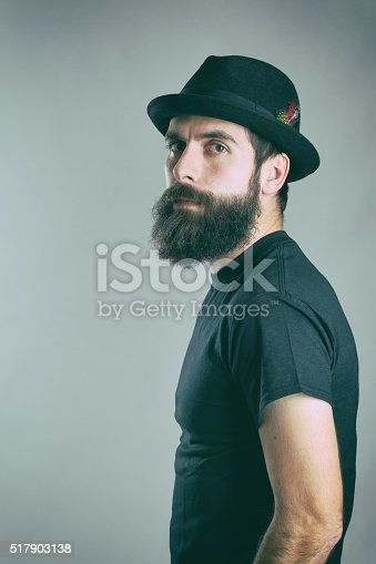 Side view of tough bearded macho man wearing black t-shirt and hat looking at camera. Retro toned filtered portrait over gray background with vignette effect.