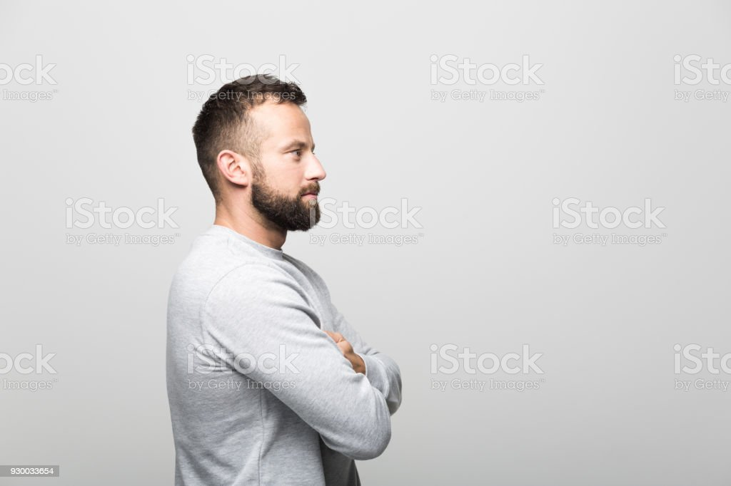 Side view of bearded young man, grey background Side view od serious bearded young man standing with arms crossed. Studio shot, grey background. 30-34 Years Stock Photo