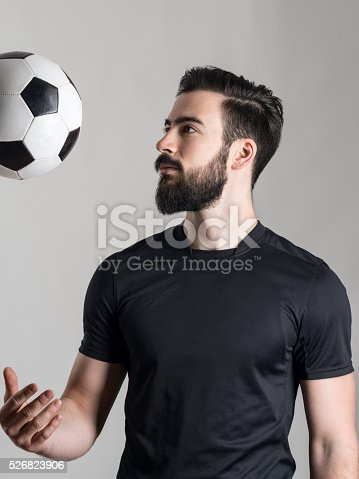 istock Side view of bearded young soccer player throwing ball 526823906
