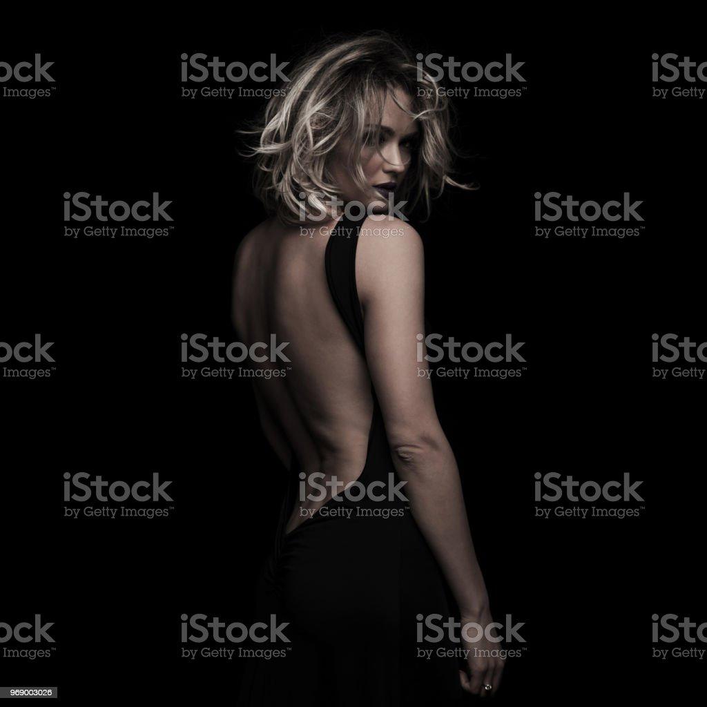side view of beautiful blonde woman wearing black backless dress stock photo