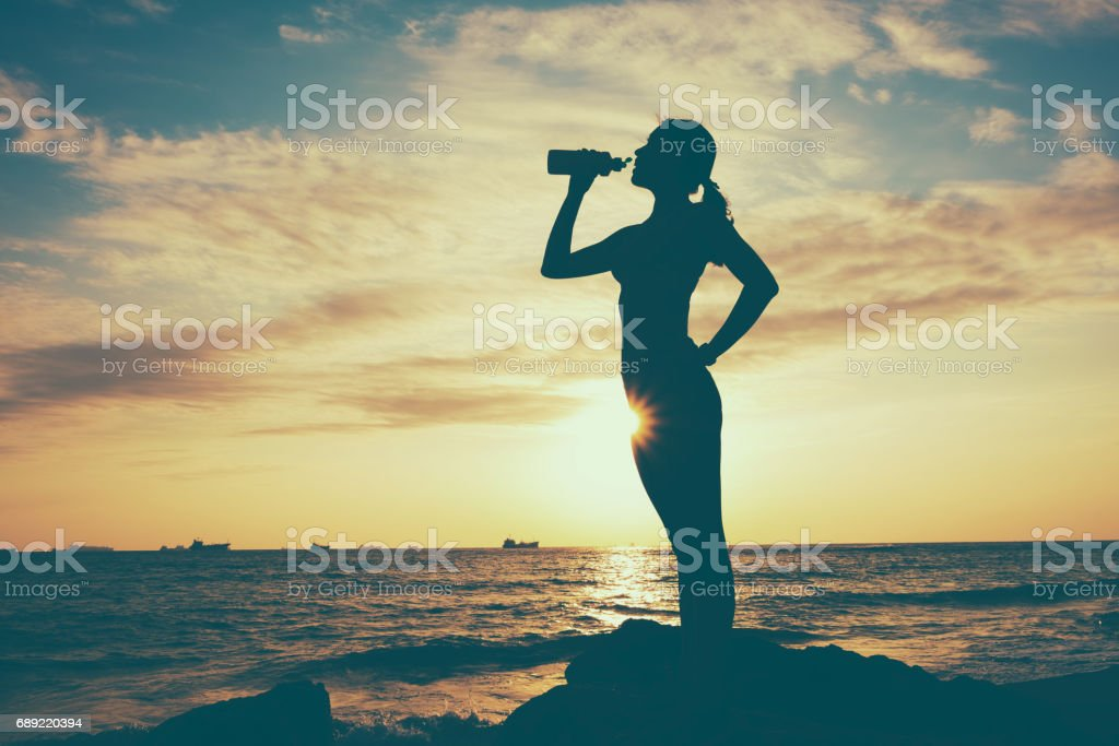 Side view of beautiful girl in sport clothes drinking water after workout on the beach stock photo