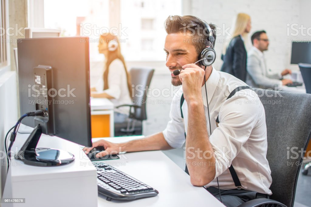 Side view of beautiful handsome operator man agent with headset working in call centre stock photo