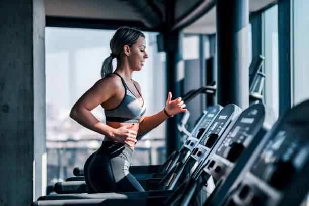 side view of beautiful muscular woman running on treadmill. - palestra foto e immagini stock