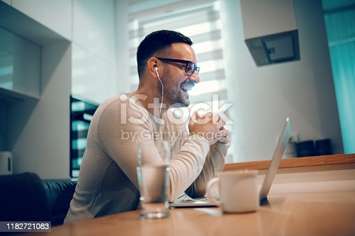 Side view of beautiful positive man dressed casual sitting at dining table in kitchen and having video call over laptop with his girlfriend. On table next to laptop are glass of water and coffee.