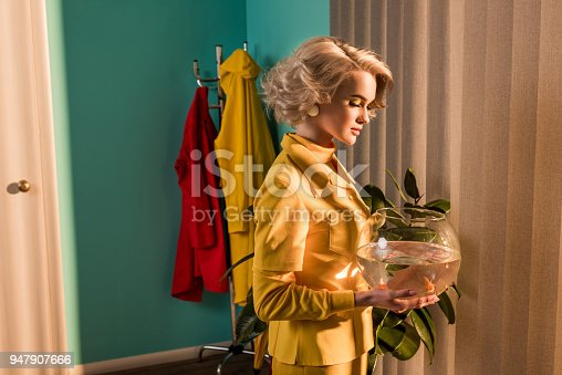 109350576 istock photo side view of beautiful stylish woman looking at aquarium with gold fish at home 947907666