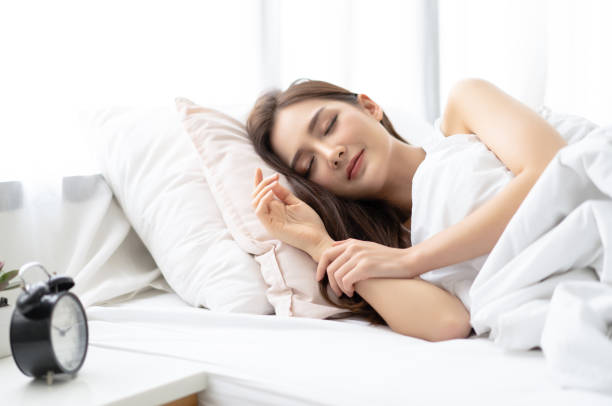 Side view of beautiful young Asian woman smiling while sleeping in her bed and relaxing in the morning. Lady enjoying sweet dreams and enough rest concept Side view of beautiful young Asian woman smiling while sleeping in her bed and relaxing in the morning. Lady enjoying sweet dreams and enough rest concept sleeping stock pictures, royalty-free photos & images