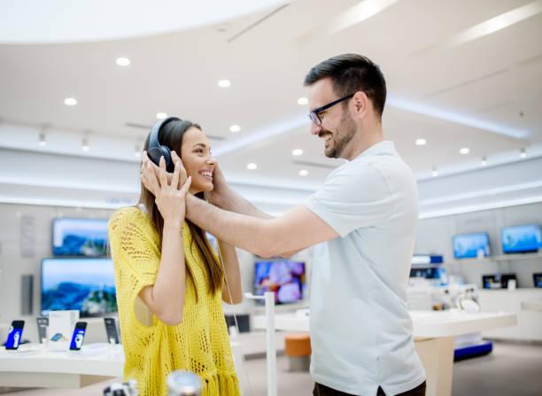 Seitlicher Blick auf schöne stilvolle liebenswert Jugendliebe Paar Kopfhörer in einem Tech-Shop testen. – Foto