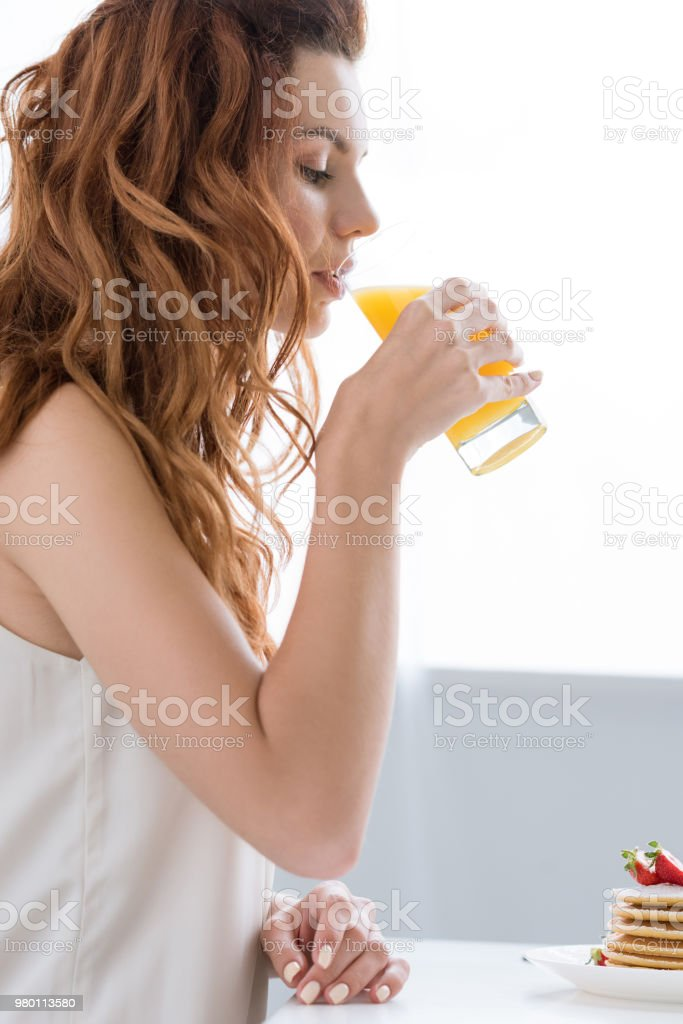 side view of beautiful young woman drinking orange juice at home stock photo