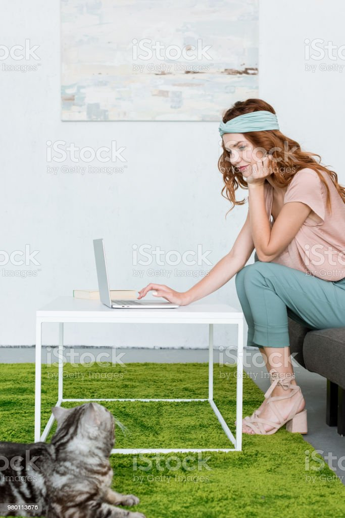 side view of beautiful young woman working with laptop while her cat lying on floor at home stock photo