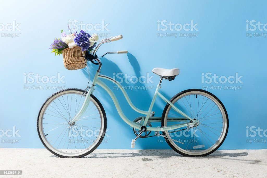 side view of bicycle with flowers in basket in front of blue wall stock photo