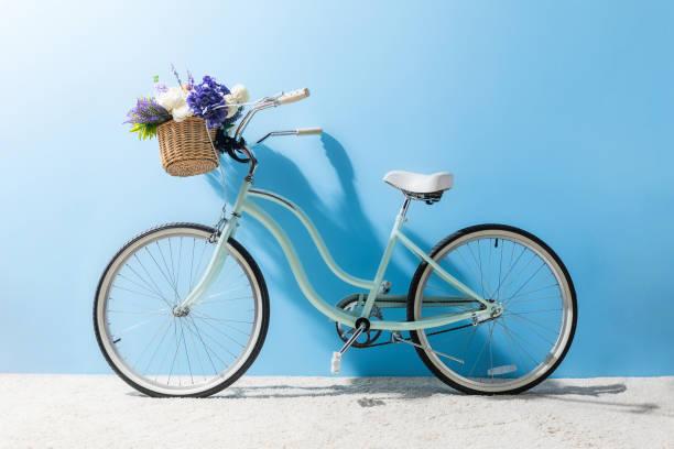 vue latérale du vélo avec des fleurs dans le panier devant mur bleu - velo photos et images de collection