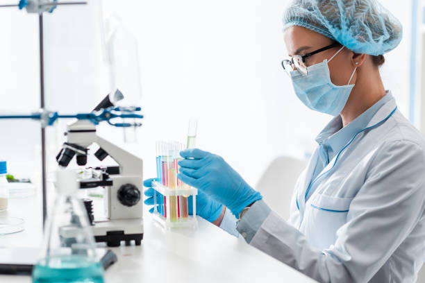 side view of biologist looking at test tube in lab stock photo